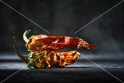 Two dried red chilli peppers in front of a dark background