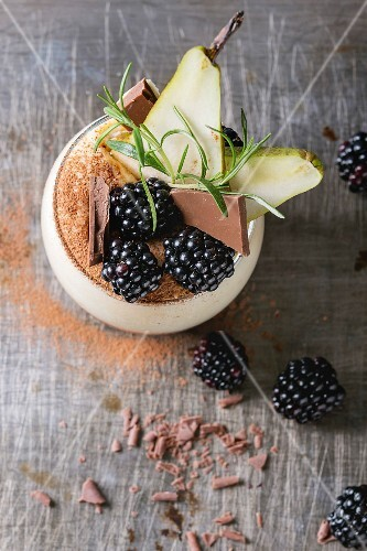Dessert breakfast layered chia seeds, chocolate pudding, rice porridge in glass decorated by fresh blackberries, sliced pear, cocoa powder