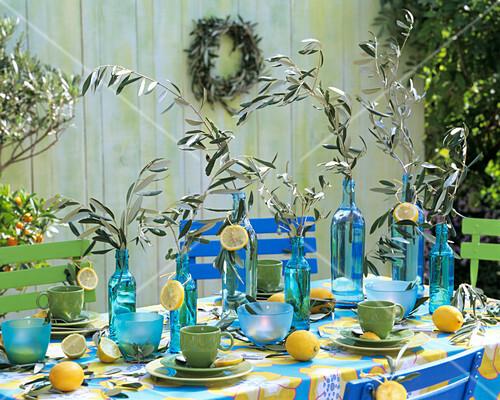 gedeckter tisch mit blauen flaschen und olivenzweigen bild kaufen 199283 stockfood. Black Bedroom Furniture Sets. Home Design Ideas