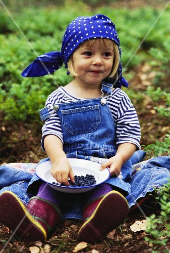 Small girl with plate of blueberries in field