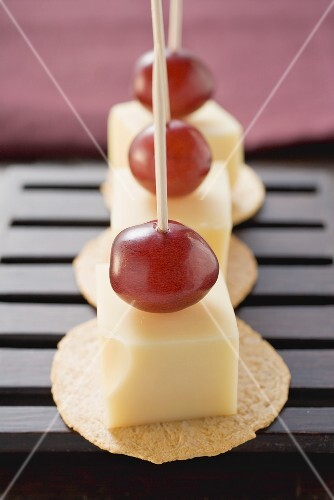 Cheese and grapes on cocktail sticks on crackers