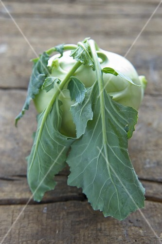 Kohlrabi with leaves on wooden background