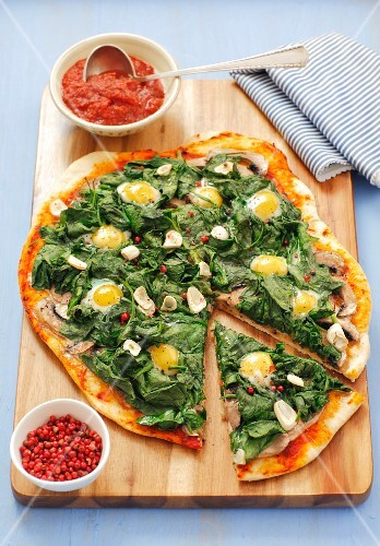 Pizza topped with spinach and quails' eggs