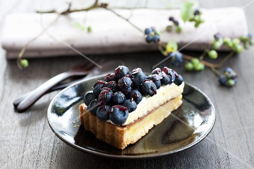 A piece of blueberry cake with jam and butter cream