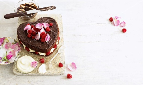 Heart-shaped cake with raspberries, cream and rose petals