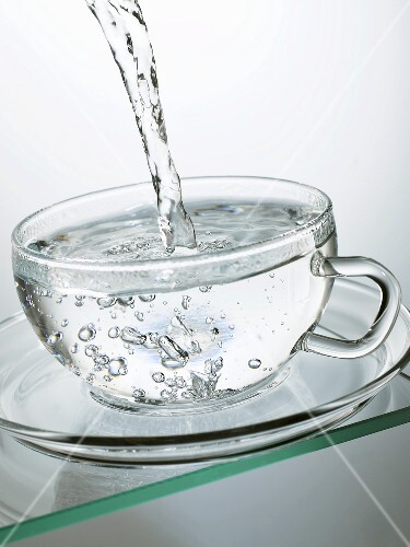 Pouring hot water into a glass cup – buy images – StockFood