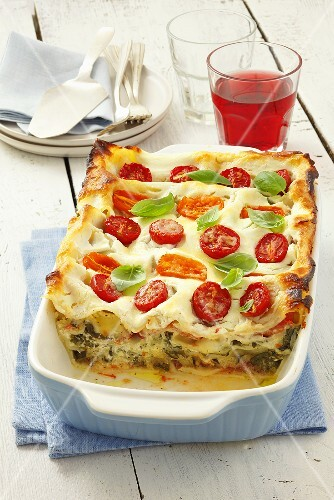 Vegetable lasagne topped with tomatoes and basil