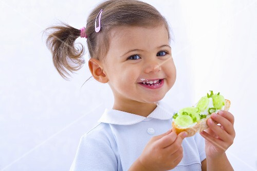 Little girl holding slice of bread with cucumber, quark and chives