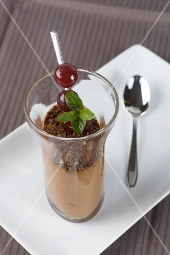 Chocolate mousse with cherries and mint leaves