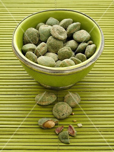 Wasabi peanuts in a green bowl on a bamboo mat