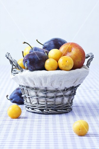 Various types of plums in a basket