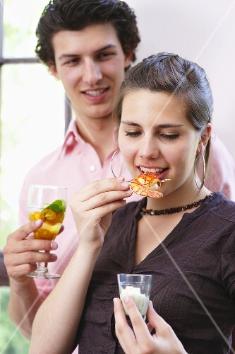 Woman eating chilli prawns, man holding drink at tapas buffet