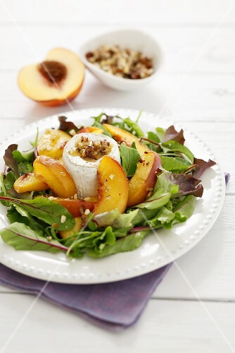 Salad leaves with peach slices, goat's cheese & walnut dressing