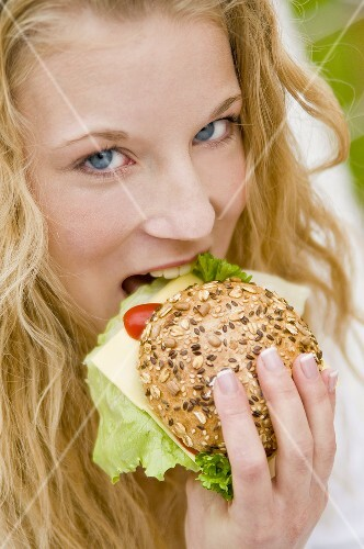 Young woman eating a filled mixed seed roll