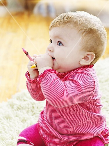 Baby playing with crayons