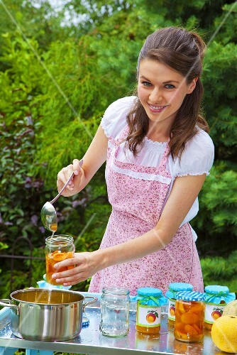 A young woman filling jars with apricot jam