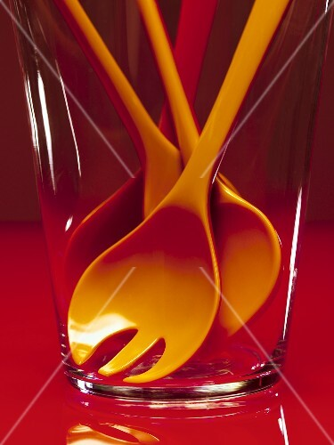 Cooking spoons (red and orange) in a glass