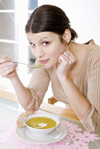 Young woman eating cream of pea soup