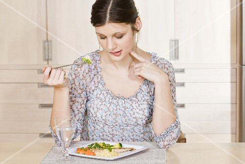 Young woman eating fish with couscous and vegetables