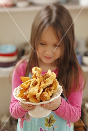 A girl holding a plate of faworki (deep-fried pastry, Poland)