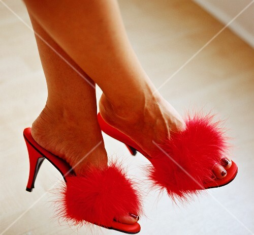 A woman wearing great, high-heeled shoes with fluffy pom-poms