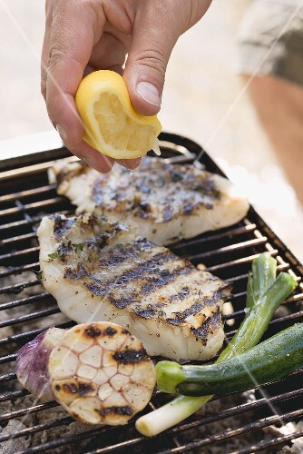 Hand squeezing lemon juice over grilled fish fillets
