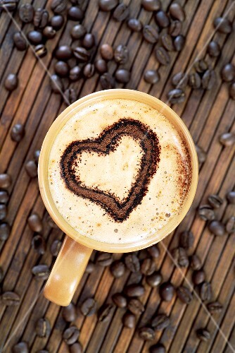 Cappuccino with heart decoration in milk foam & coffee beans