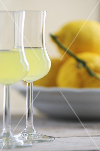 Two glasses of limoncello, lemons in background