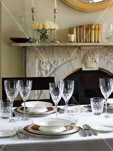 Elegantly laid table in front of fireplace