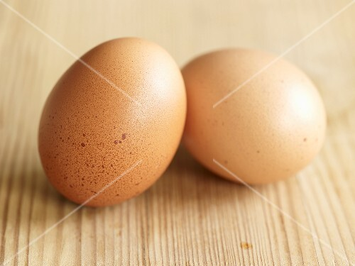 Two hens' eggs on wooden background