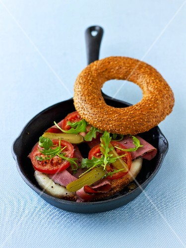 Toasting a bagel with pastrami in a pan