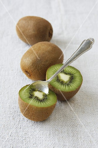 Kiwis, whole and halved, with a spoon