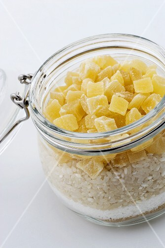A jar of brown sugar, coconut shavings, rice and dried pineapple pieces