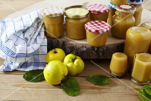Several jars of quince jam and fresh quinces
