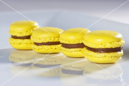 Four yellow macaroons with chocolate cream