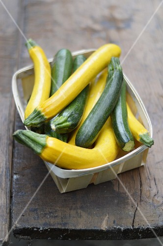 Punnet of yellow and green courgettes