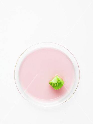 Piece of green tomato on a pink circle