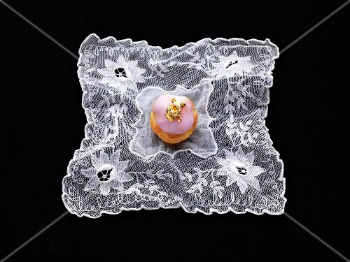 Small pink cream puff decorated with a golden leaf on a lace cloth