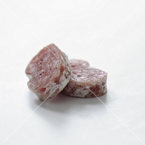 Slices of dried sausage on a white background