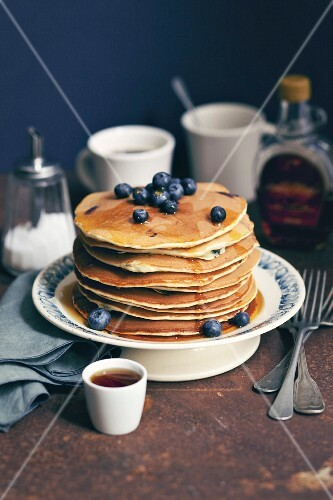 Pile of pancakes with maple syrup and blueberries