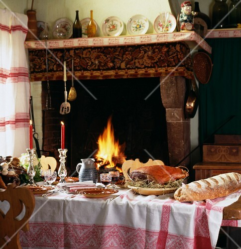Set table with cured ham on bed of hay and fireplace