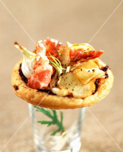 Individual flaky pastry tart filled with potatoes, onions and bacon