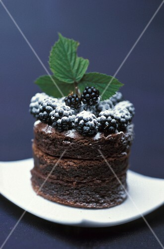 A mini chocolate cake with blackberries