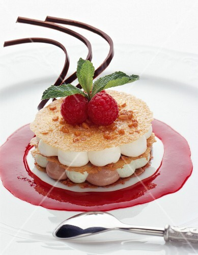 Crispy layer cake with white chocolate on raspberry sauce