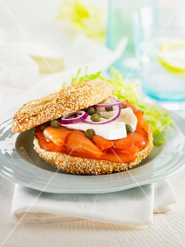 A bagel with smoked salmon, Brie, capers and red onions