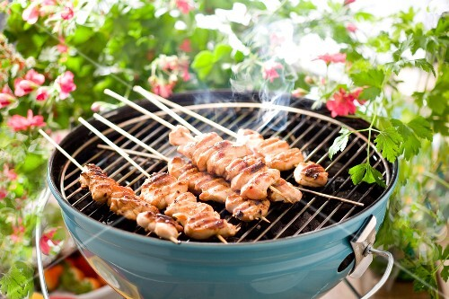 Chicken kebabs cooking on the barbecue in the garden