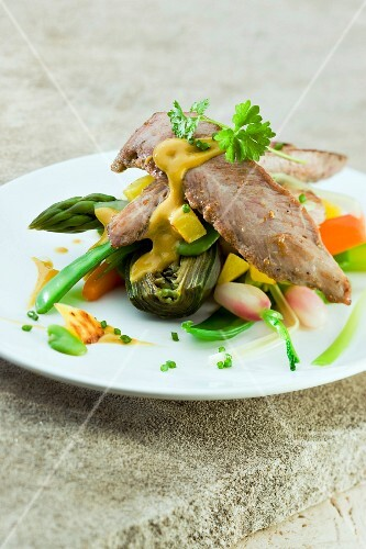 Sliced duck breast with spring vegetables