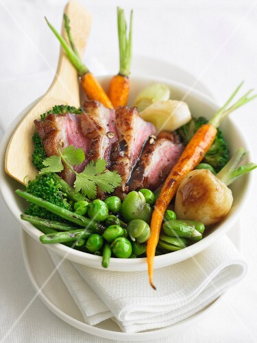 Young vegetables sauteed in a wok, sliced duck breast