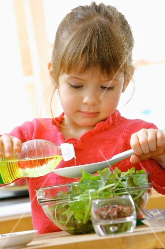 Young girl preparing a french dressing for the salad