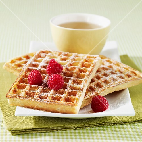 Wafles with icing sugar and raspberries